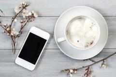 La tasse du café et du smartphone sur la table en bois avec la cerise fleurit, vue supérieure Photographie stock