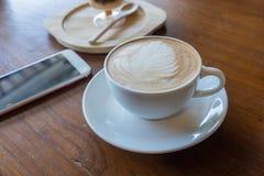 La tasse du smartphone chaud d'annonce de café a mis dessus le vieux backgrou en bois de table Photo stock