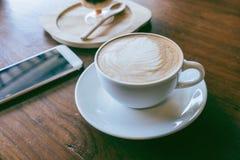 La tasse du smartphone chaud d'annonce de café a mis dessus le vieux backgrou en bois de table Photographie stock