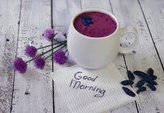 La tasse du smoothie de kenette avec des fleurs d'été et bonjour textotent sur la serviette blanche Photo libre de droits