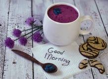 La tasse du smoothie de kenettes avec des fleurs d'été, la cuillère, les biscuits et bonjour textotent Images libres de droits
