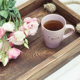 La tasse du thé chaud et de l'eustoma rose fleurit contre les jeunes jaunes blancs de source de fleur de concept de fond Photographie stock libre de droits