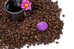 La tasse en acier décorée d'une fleur dans les grains du café noir Images stock