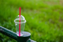La tasse en plastique a un couvercle par utiliser-et alors mis de côté sur la pelouse photo stock