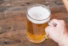 La tasse en verre de bière se tenant sur un vieux fond en bois, main femelle se tient photo stock