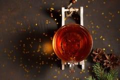 La tasse en verre de thé sur le traîneau en bois avec le sapin s'embranche sur le fond en pierre brun avec les étoiles d'or Photo stock