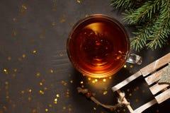 La tasse en verre de thé, de traîneau et de sapin s'embranche sur le fond en pierre brun avec les étoiles d'or Photos libres de droits