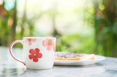 La tasse mignonne de plan rapproché sur la vue de marbre brouillée de bureau et de jardin pendant le matin a donné au fond une co Photos stock