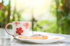 La tasse mignonne de plan rapproché sur la vue de marbre brouillée de bureau et de jardin pendant le matin a donné au fond une co Images stock