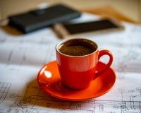 La tasse orange de café chaud préparé frais se tient sur des dessins et un s Photographie stock