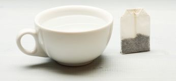 La tasse a rempli d'eau bouillante et de sac à thé sur le fond blanc Concept de temps de thé Processus de thé brassant dans la ta Images stock