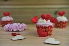 La tasse romantique de jour de quelques valentines durcit avec les décorations rouges de coeur d'amour sur les roses de papier su Photo libre de droits