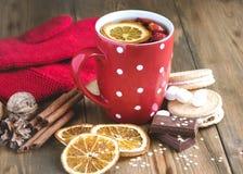 La tasse rouge de thé chaud avec les bâtons en bois de Cinnamone de fond de concept de nourriture de Noël de boisson d'hiver d'or image stock