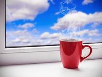 La tasse se tient sur un rebord de fenêtre Photo libre de droits