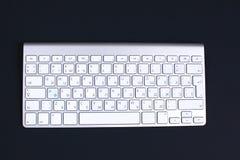 La tastiera di alluminio alla moda si trova su una tavola nera Fotografia Stock Libera da Diritti