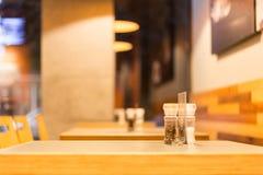 La tavola del ristorante del pepe e del sale interna svuota fotografia stock
