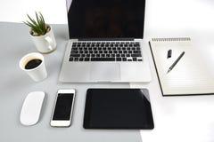 La tavola dell'ufficio con il computer portatile, il taccuino, la compressa digitale e lo smartphone su due moderni tonificano il Immagini Stock Libere da Diritti