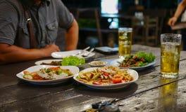 La tavola di Dinning con alimento in ristorante e due vetri della birra con l'uomo si siedono nell'opposto Fotografia Stock Libera da Diritti
