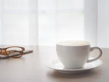la tavola di legno con la tazza di caffè calda e gli occhiali moderni su bianco confuso coprono il fondo Fotografia Stock