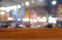 La tavola di legno scura vuota davanti all'estratto ha offuscato il fondo dell'interno della caffetteria e del caffè Può essere u fotografie stock