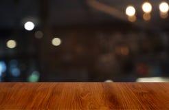 La tavola di legno scura vuota davanti all'estratto ha offuscato il fondo dell'interno della caffetteria e del caffè Può essere u fotografia stock libera da diritti