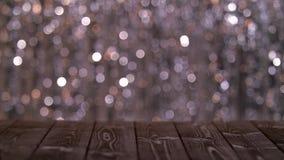 La tavola di legno sullo schermo dell'estratto scintillante ha offuscato i cerchi multicolori Fondo Bokeh stock footage