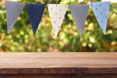 La tavola di legno vuota con le bandiere fa festa il fondo all'aperto per pro Fotografie Stock