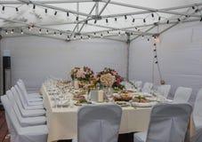 La tavola di nozze nel ristorante della campagna decorato con il rosa fiorisce i vetri fotografie stock libere da diritti