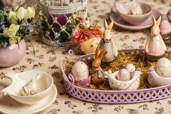 La tavola di prima colazione di Pasqua con tè, uova in portauova, molla fiorisce in vaso e decorazione di Pasqua Immagini Stock