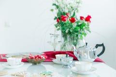 La tavola di tè, le tazze di tè della porcellana, la teiera d'argento, casa ha prodotto i biscotti Immagine Stock