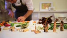 La tavola di taglio con vari frutti di mare nel cuoco unico del fondo prepara, movimenti della camma a sinistra, cambiamento dina stock footage