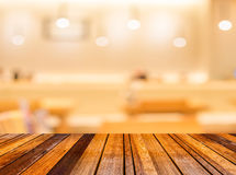 La tavola e la caffetteria di legno vuote offuscano il fondo con il imag del bokeh Immagini Stock Libere da Diritti