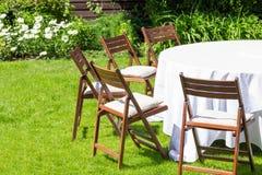 La tavola rotonda coperta di panno bianco e le sedie stanno su un prato inglese verde all'aperto Fotografia Stock Libera da Diritti
