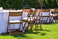 La tavola rotonda coperta di panno bianco e le sedie stanno su un prato inglese verde all'aperto Immagine Stock