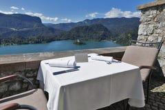 La tavola servita con il piatto vuoto, lago ha sanguinato, isola ed alpi Fotografie Stock Libere da Diritti