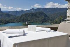 La tavola servita con il piatto vuoto, lago ha sanguinato, isola ed alpi Fotografie Stock