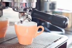 La taza anaranjada del coffe se prepara para el café express fotos de archivo