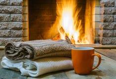 La taza anaranjada para el té o el café, las cosas de lana acerca a la chimenea acogedora Imagen de archivo libre de regalías