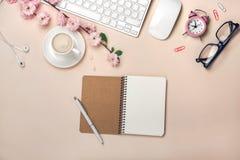 La taza blanca con el capuchino, Sakura florece, teclado, despertador, cuaderno en un fondo del rosa en colores pastel imagen de archivo