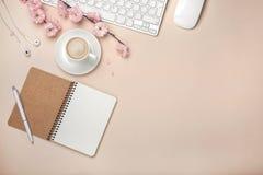 La taza blanca con el capuchino, Sakura florece, teclado, despertador, cuaderno en un fondo del rosa en colores pastel fotografía de archivo