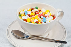 La taza blanca con la cuchara en la placa llenó de las píldoras Imagen de archivo