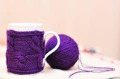 La taza blanca con la violeta hizo punto el suéter en ella con la bola del hilado Foto de archivo
