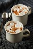 La taza blanca de cacao caliente fresco o de chocolate caliente con las melcochas en gris hizo punto el fondo Fotos de archivo libres de regalías