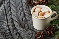 La taza blanca de cacao caliente fresco o de chocolate caliente con las melcochas en gris hizo punto el fondo Fotografía de archivo