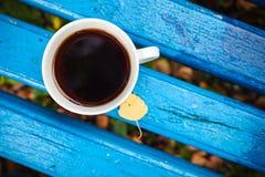 La taza blanca de té negro está en banco de madera viejo Fotos de archivo