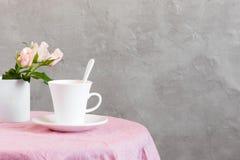 La taza blanca de té o de café con leche en la tabla cubrió ingenio foto de archivo