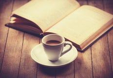 La taza blanca del café y el vintage reservan. Imagen de archivo