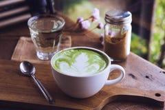 La taza blanca del latte caliente de la bebida del té verde en el aroma de madera de la tabla relaja el ti imágenes de archivo libres de regalías