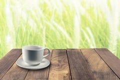 La taza blanca en la tabla y la hierba borrosa florece en fondo Fotos de archivo