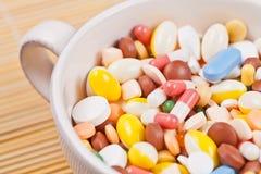 La taza blanca llenó de las píldoras de la medicina Foto de archivo